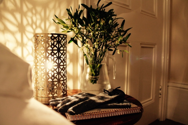 Bedside table featuring Moroccan style lamp, jug of mistletoe, acorn notepad and grey gloves
