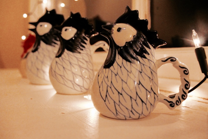 Chicken jugs on a window sill surrounded by glowing fairy lights