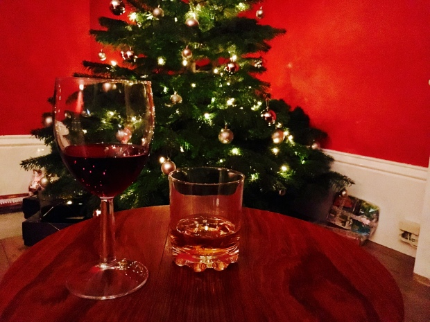 A glass of red wine and a glass of whiskey in front of a Christmas tree