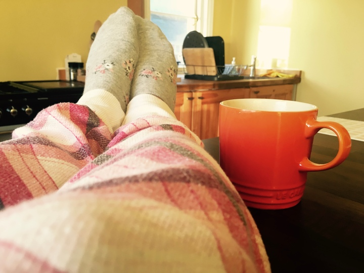 Feet on a kitchen table beside a Le Creuset mug in a sunny yellow kitchen
