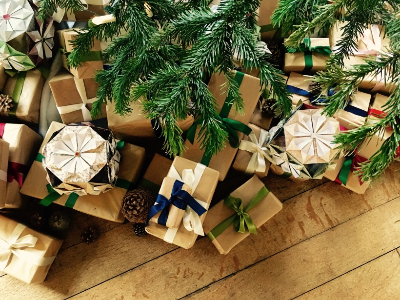 Christmas presents wrapped in brown paper and tied with silk ribbons underneath a tree.