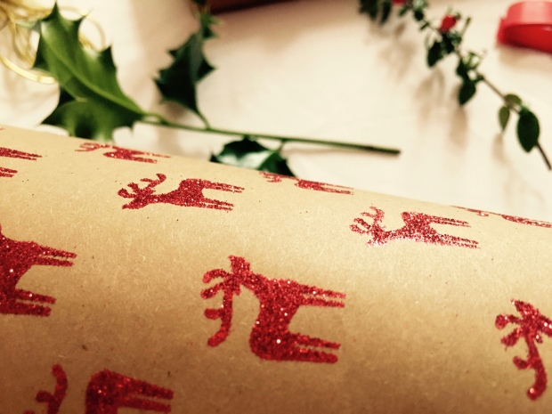 Christmas wrapping paper with holly, ribbons and gold ties in the background