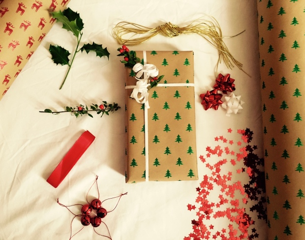 Christmas present surrounded by paper, ribbons, stars, bows and foliage
