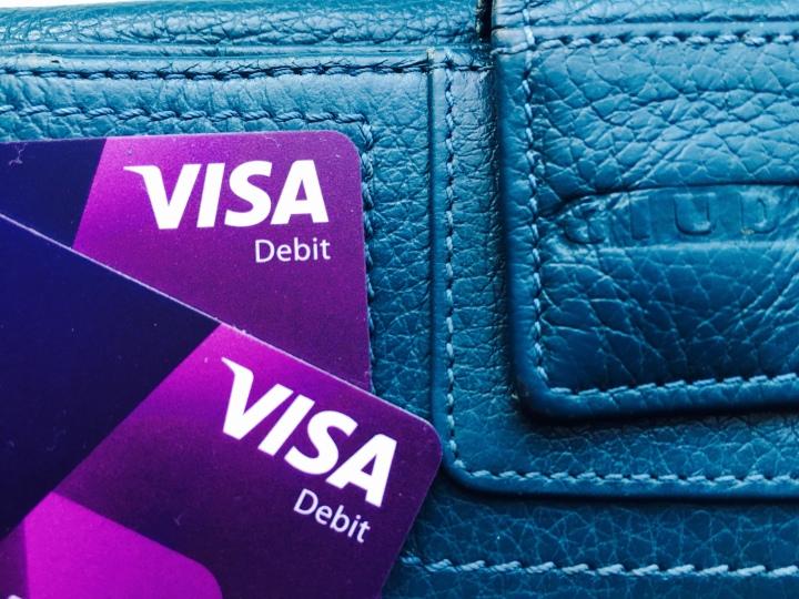 Visa cards sitting on top of a ladies wallet