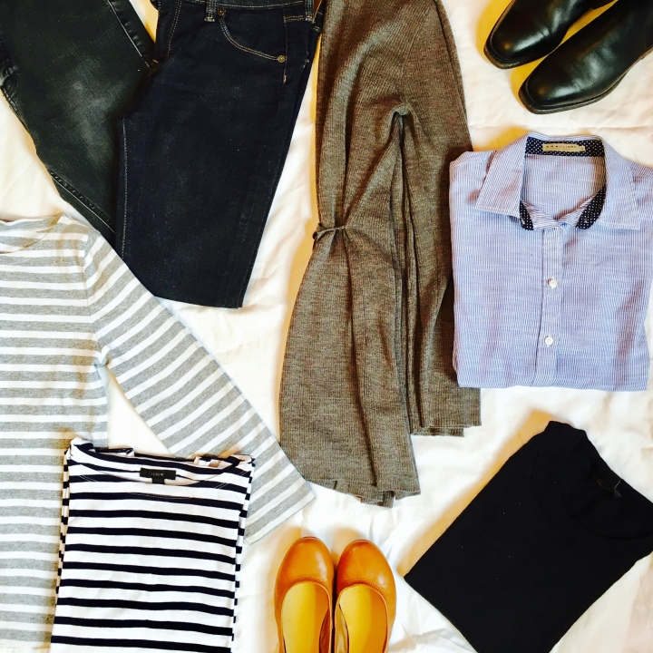 Flat lay of long weekend capsule wardrobe focused on stripes and black, grey and blue.