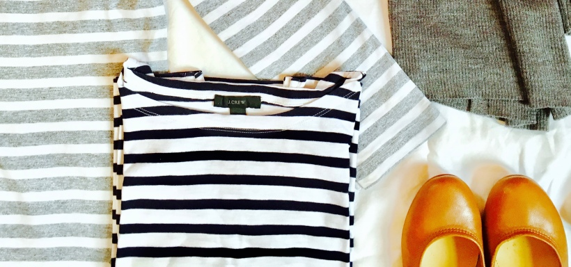 Flat lay of striped t-shirts, ballet flats and a cardigan.