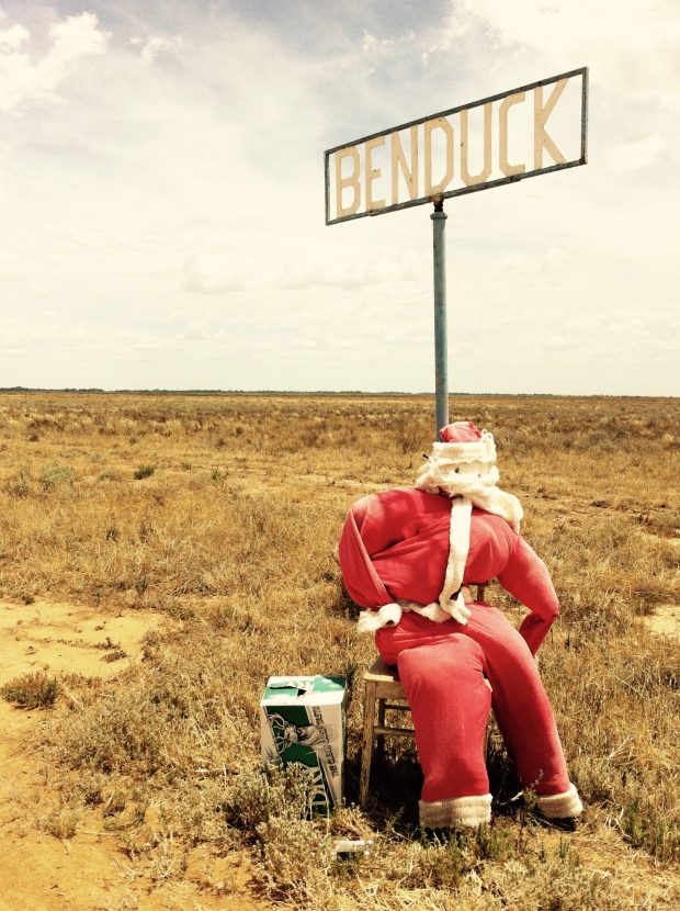 Santa Clause mannequin sitting beside a property name sign in western New South Wales, Australia