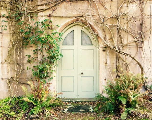 Ivy and ferns cover the front entrance of a house with a sage green arched door.