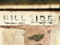 'Hill Side' name etched into sandstone pillar outside English house