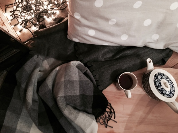 Exploring the Danish concept of hygge: fairylights in fireplace, grey cushions and throw rugs, pot of tea.