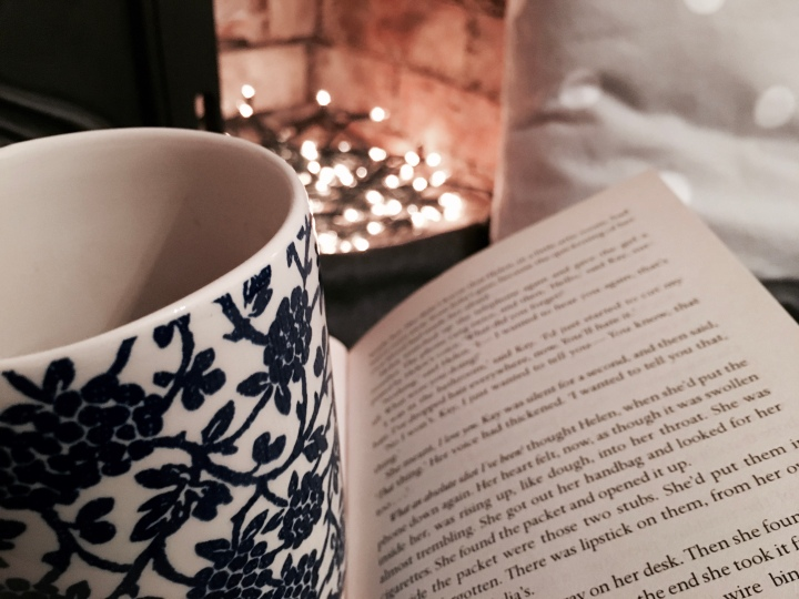 Embracing the Danish concept of hygge: drinking tea, reading a book under soft grey throw rugs in front of a fireplace lit with fairy lights
