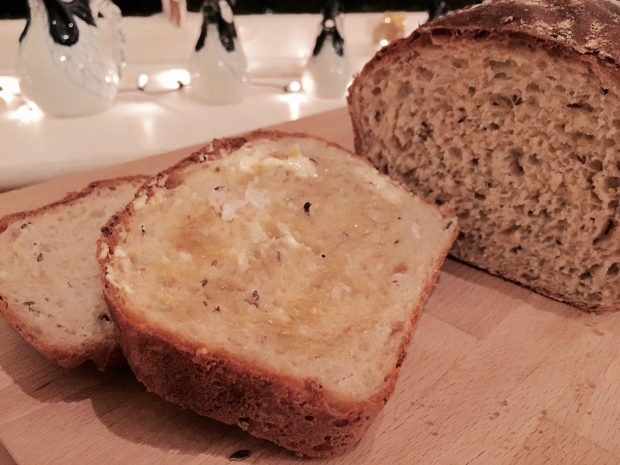 Freshly baked loaf of honey and seed bread spread with butter, honey and sprinkled with salt flakes