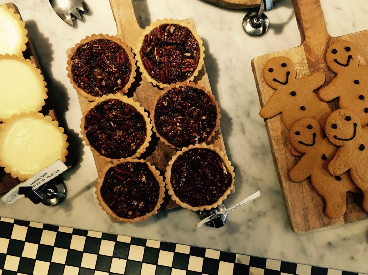 Lemon tarts, pecan tarts and gingerbread displayed on wooden boards on marble table sitting on a black and white checkered tile floor