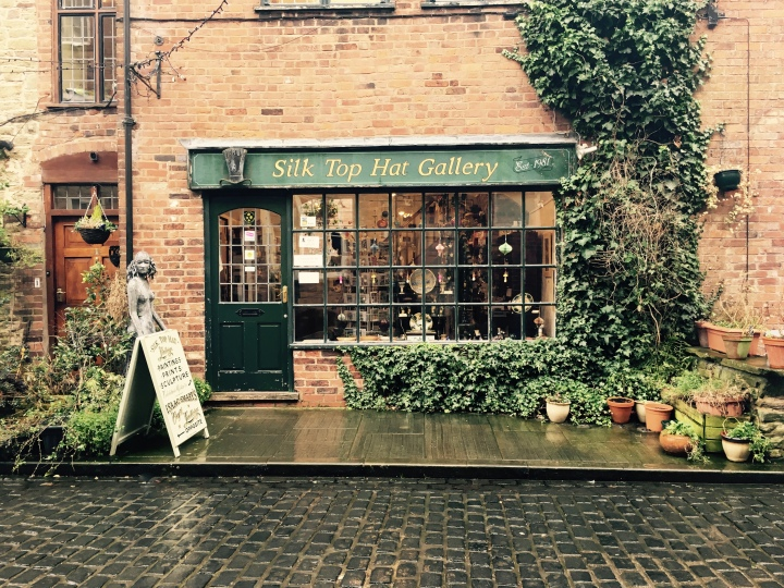 Shop in brick building covered in ivy, on cobblestone lane in Ludlow, Shropshire