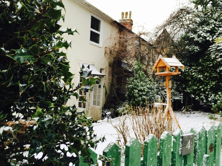 Snow covered front yard of Georgian house with bird feeder