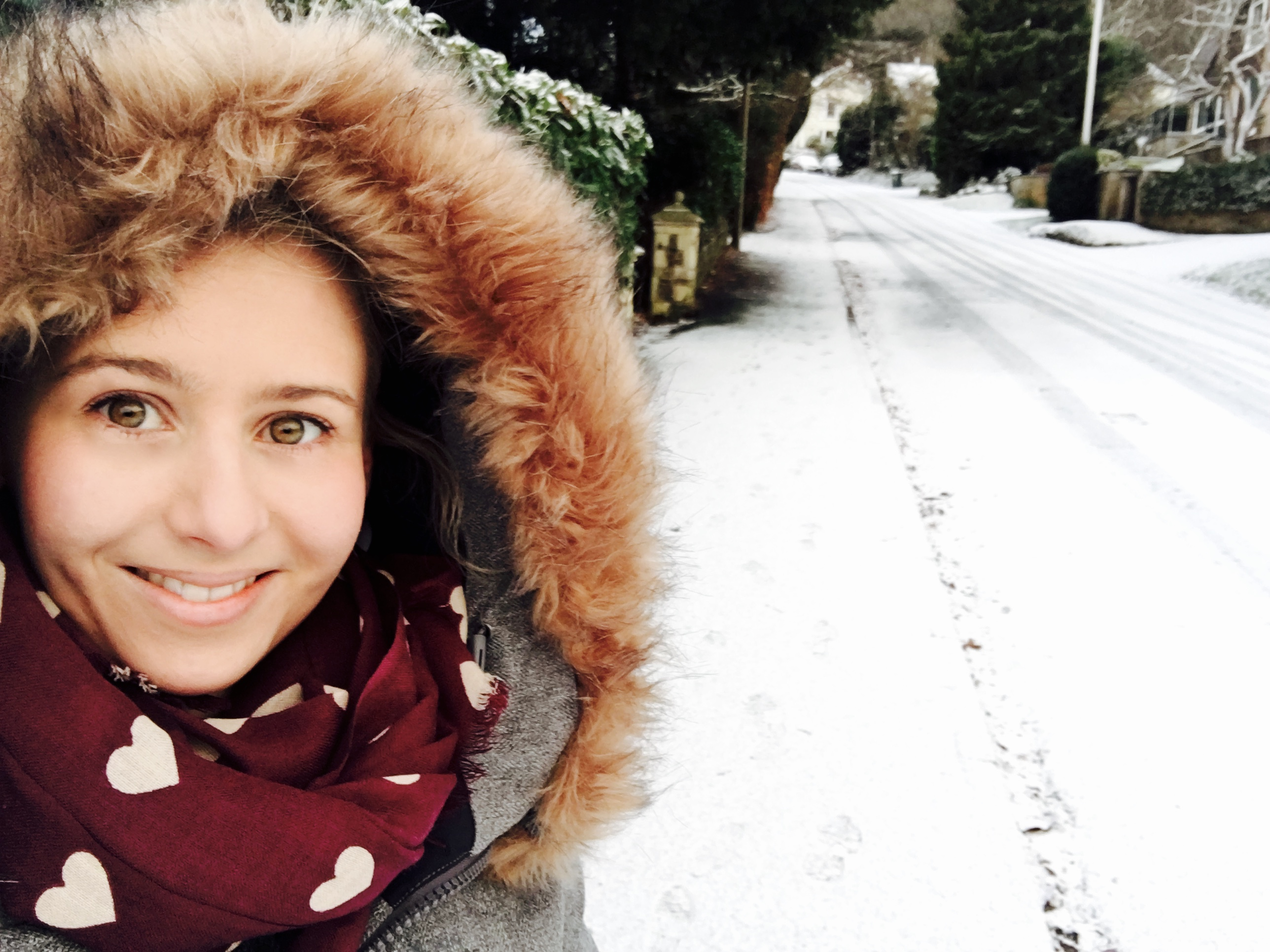 Girl standing in snowy street with scarf and hooded coat on