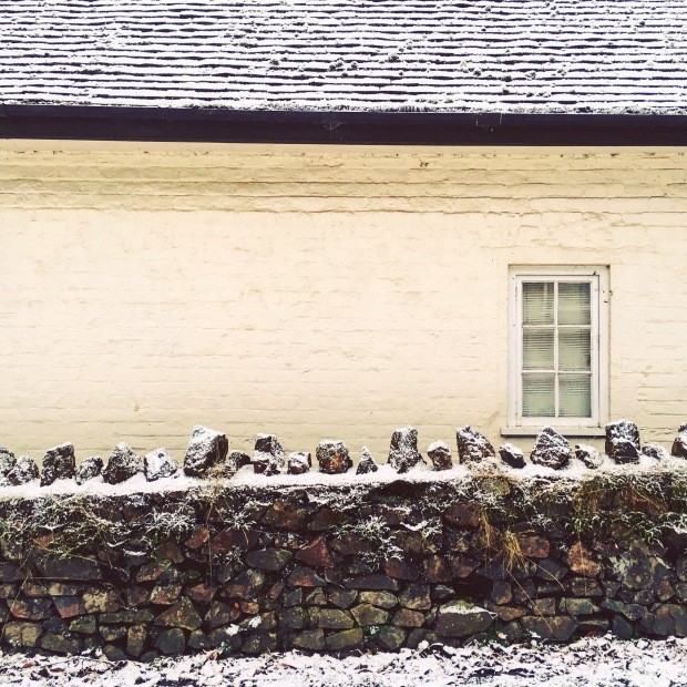 Stone cottage with dry stone wall in front of it covered in snow.