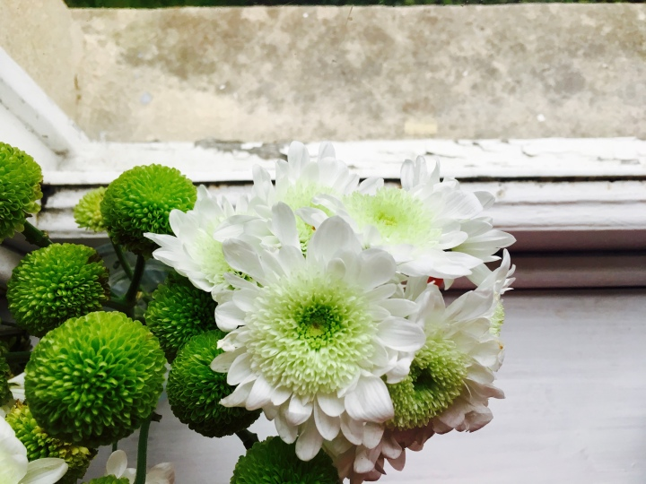 White chrysanthemum flowers and green dahlia flowers sitting in a vase on a the sill of a sash window.
