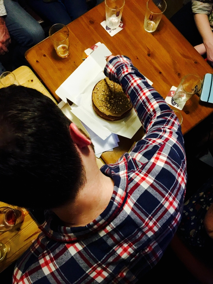 Aerial shot of man cutting a birthday cake at a pub surrounded by friends.
