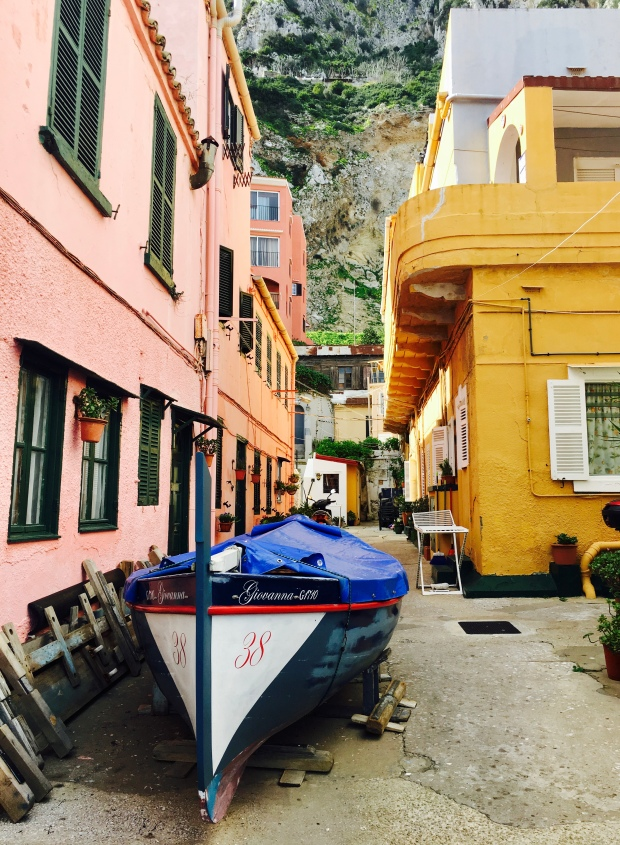 Wooden boat dry docked in front of colourful houses in Gibraltar's Catalan Bay.