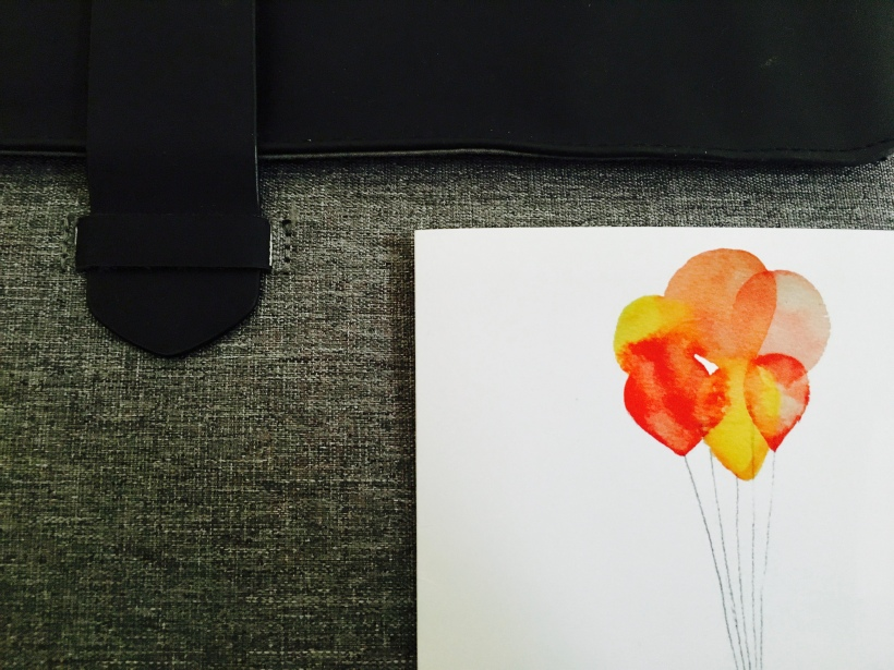 Card with red and yellow balloons leaning up against a grey and black pouch.
