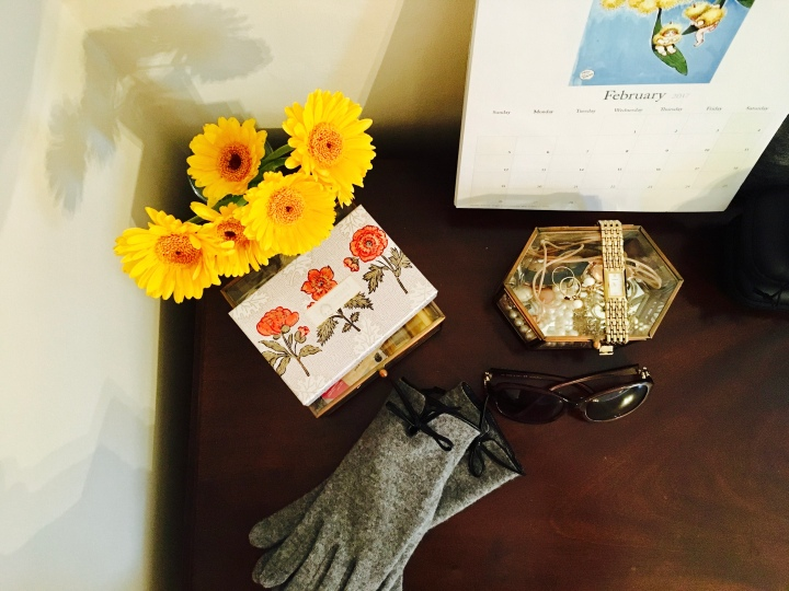 Top of a dressing table featuring calendar, flowers, jewellery box, gloves, sunglasses and perfume.