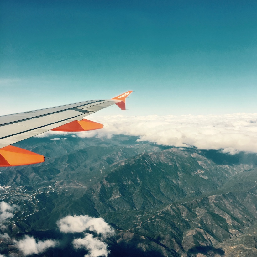 The wing of an Easy Jet plane hovering above mountains in Spain.