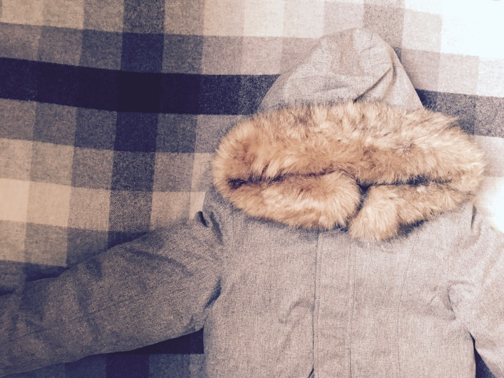 Flat lay of winter coat with fur hood.