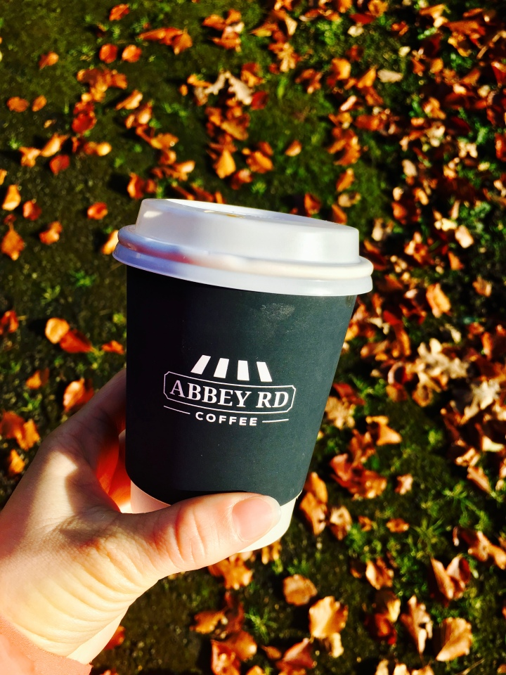 Hand holding takeaway coffee cup.