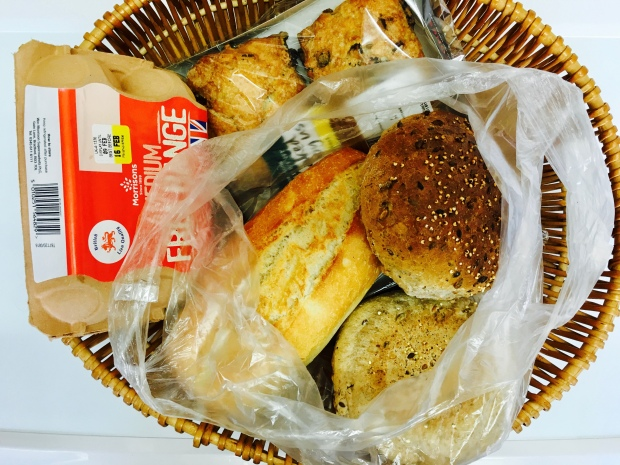 Basket of scones, bread rolls and eggs.