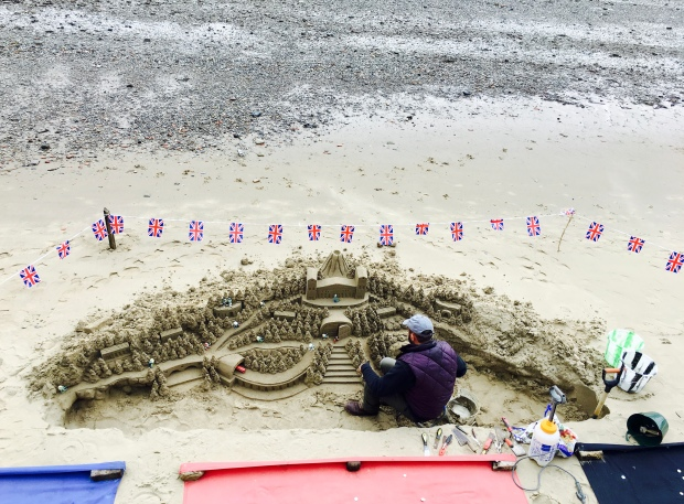 Man building a sandcastle on the banks of the Thames River, London.