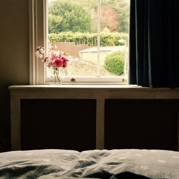 Looking from a bed onto a window sill where a bunch of pink flowers is sitting.