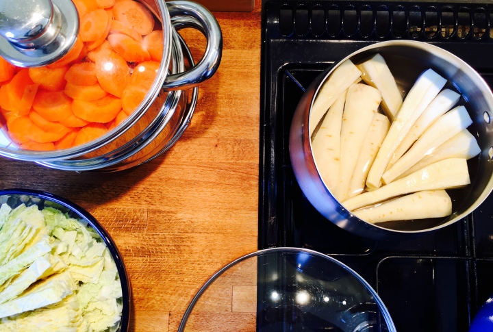 Parsnips, carrots and cabbage being prepared for a roast dinner.