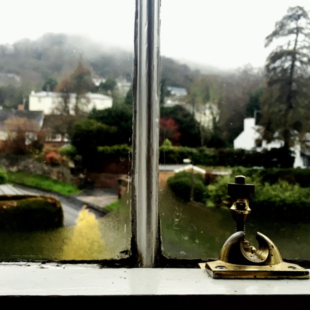 Looking out of a sash window in a Victorian era house onto a rainy day with clouds covering nearby hills.