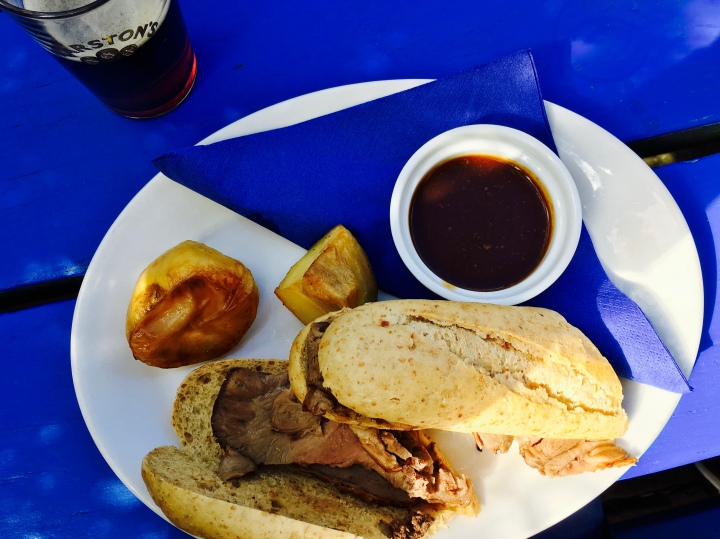 Half pint of beer with a roast lamb roll, roast potatoes and gravy.