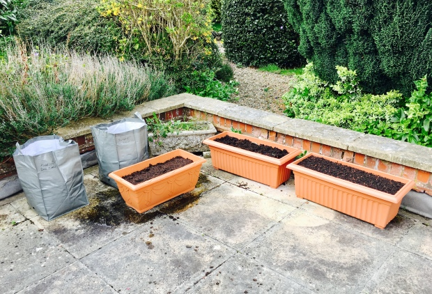 Terrace with planter bags and tubs full of soil.