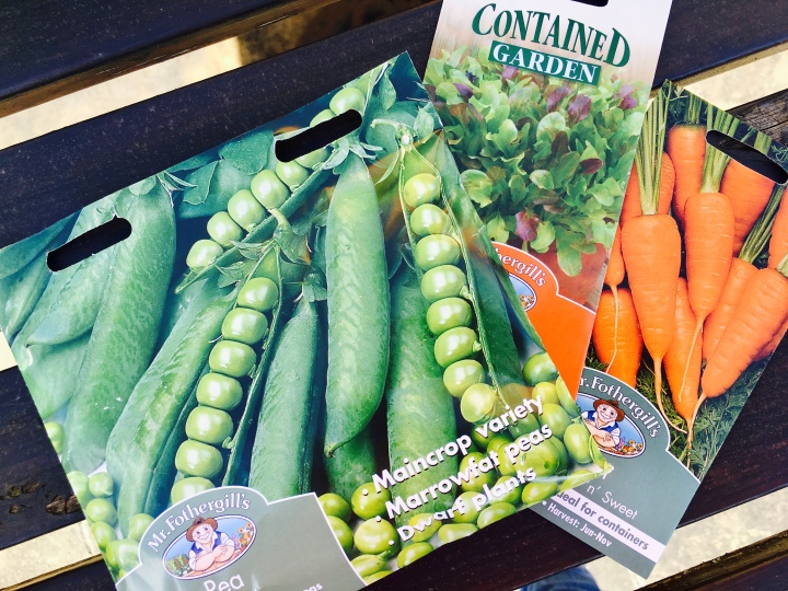 Seed packets for peas, salad leaves and carrots.