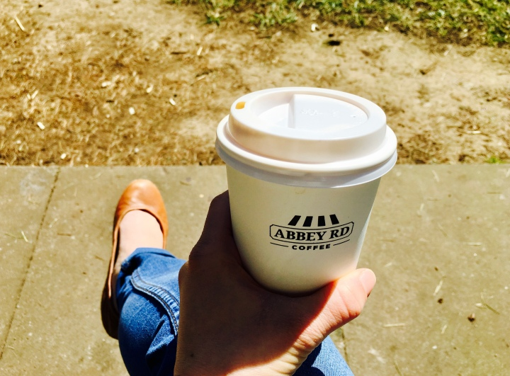 Hand holding a coffee cup in the sunshine.