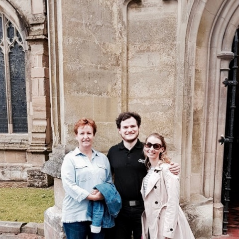 Tourists posing for a picture outside of Malvern Priory, Worcestershire.