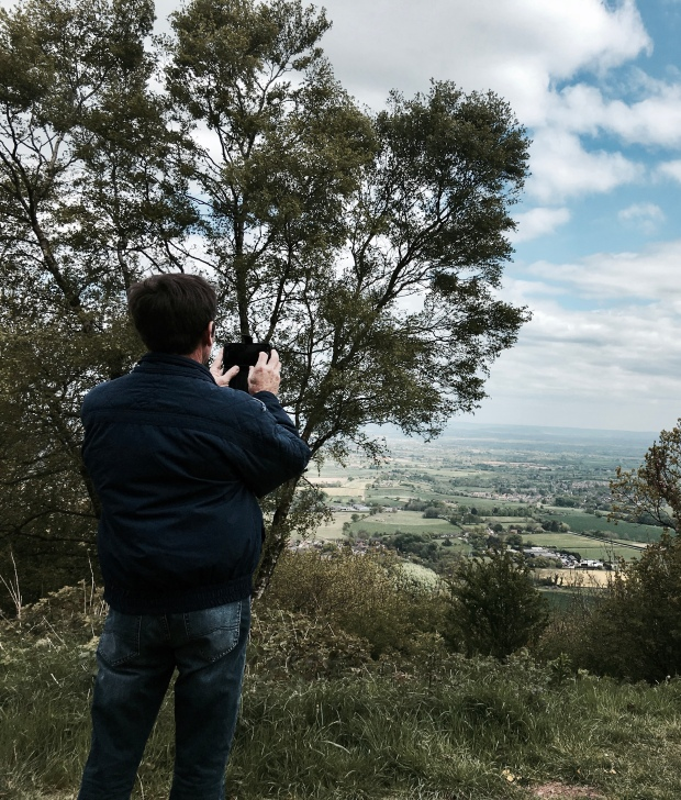 Tourist taking picture on Malvern Hills, Worcestershire.