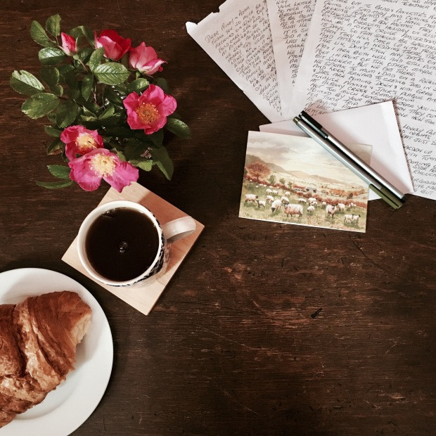 Flat lay of tea, croissant, roses, card and handwritten letter on timber table.
