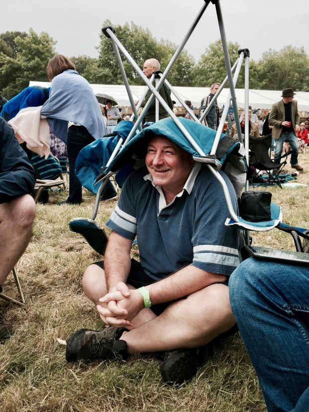 Man wearing camp chair on head to prevent getting wet in a shower of rain.