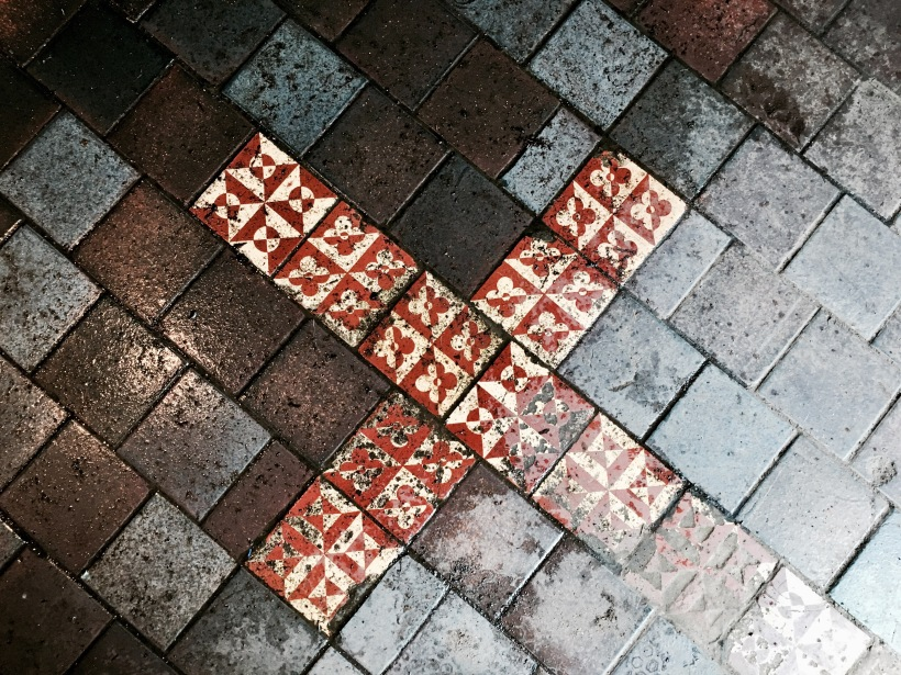 Tiled cross on the floor of Holywell, Malvern Wells, Worcestershire, England.