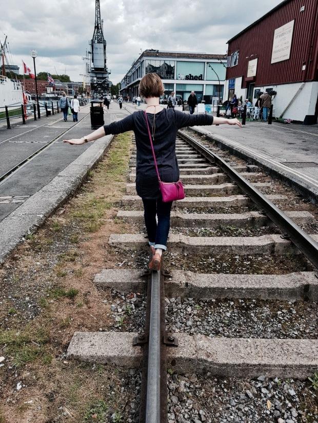 Woman balancing on disused rail tracks, Spike Island, Bristol Harbour.