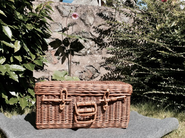 Wicker picnic basket sitting on a rug in front of a stone wall and near a pink flower.