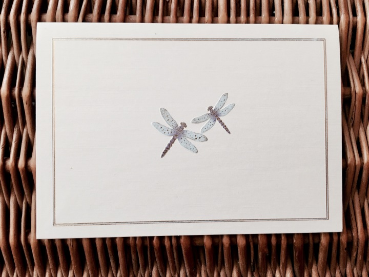 Dragonfly greeting card sitting atop a wicker picnic basket.