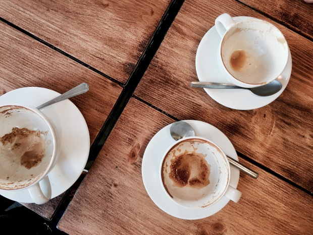 Empty coffee cups sitting on a wooden table.