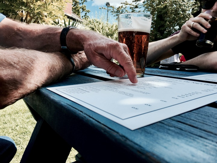 Hand pointing at a menu at a beer garden in rural England.