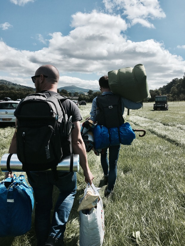 Two men carrying camping equipment onto the Green Man festival site in Wales.