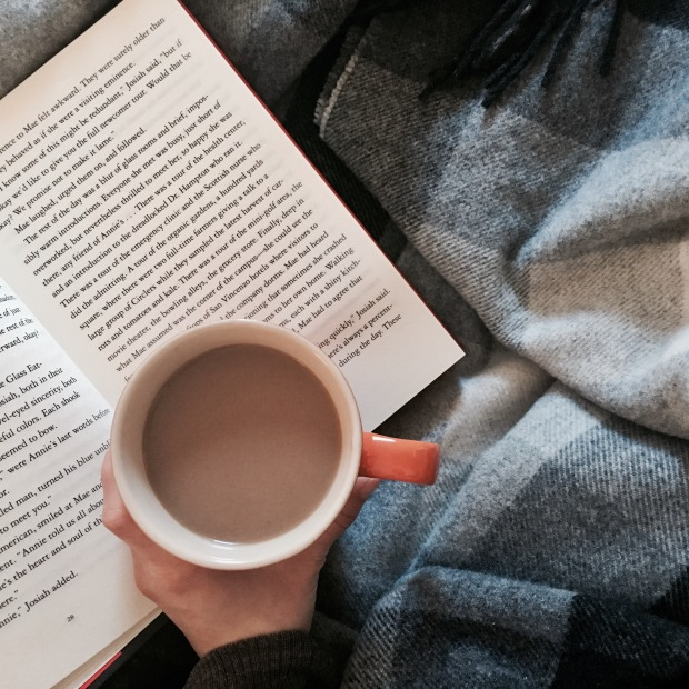 Overhead shot of a person drinking coffee and reading book under a woollen blanket.